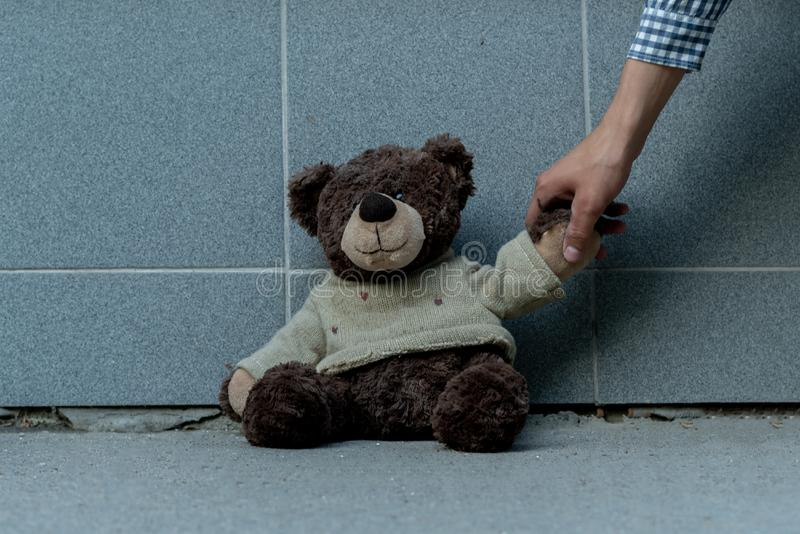 human hand grab the dirty teddy bear from the ground outdoors, lost concepts stock photo