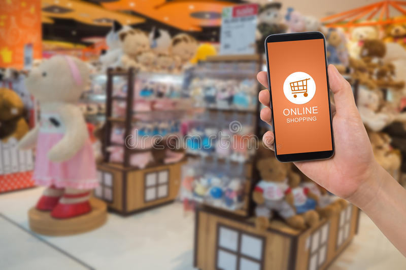 human hand hold smartphone, tablet, cell phone with online shopping application screen on blurry toy shop background. stock photography