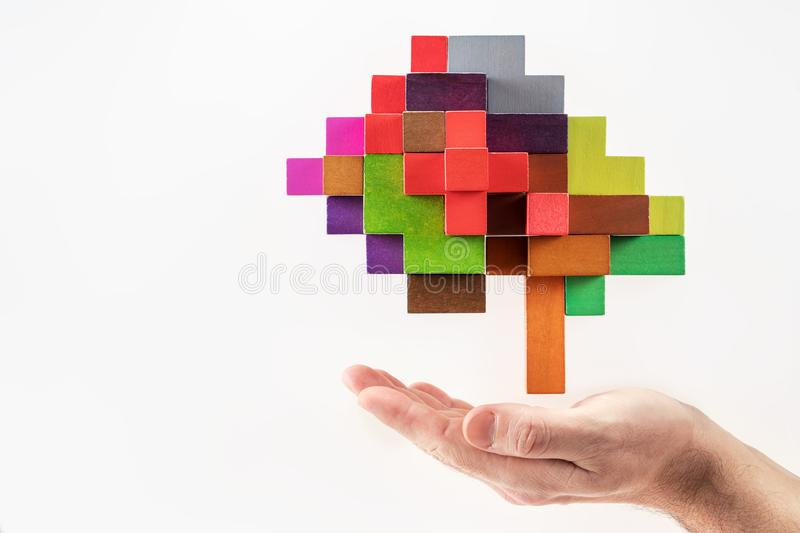 Human hand holding abstract brain. Human brain is made of multi-colored wooden blocks royalty free stock images