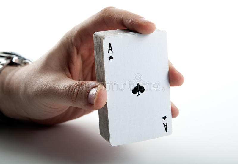 Human hand holding the ace of spades and a deck of cards stock images