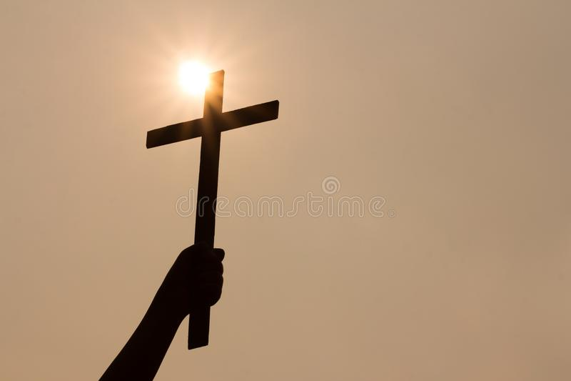 Human hand holding a cross, the background is the sunrise. stock photo
