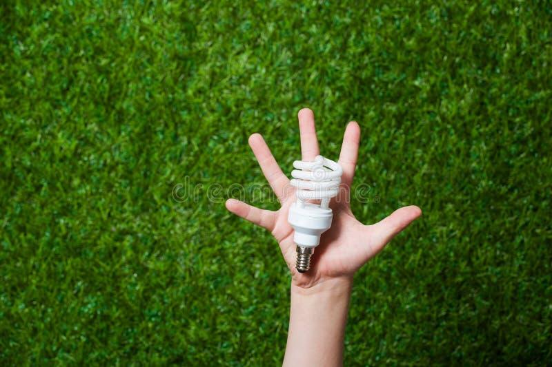 Human hand holding energy saving lamp royalty free stock images