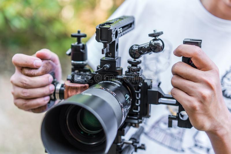 Human hand holding Full Equipment Videography set for Mirrorless small camera. Full Equipment Videography set for Mirrorless small camera for work. Handles royalty free stock images