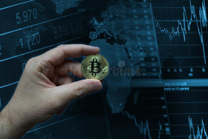 Human hand holding a golden virtual coin Bitcoin against a technological background. Global market concept. With empty copy space for Editor`s text royalty free stock images