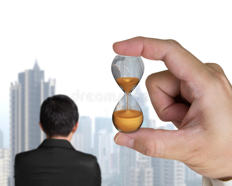 Human hand holding hourglass with businessman. Looking city skyscraper stock photos