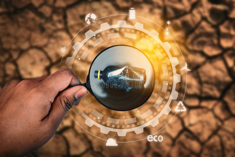Human hand holding magnifying glass with icon on crack ground outdoor on the baking hot day. Drought and environmental problems and pollution concept stock image