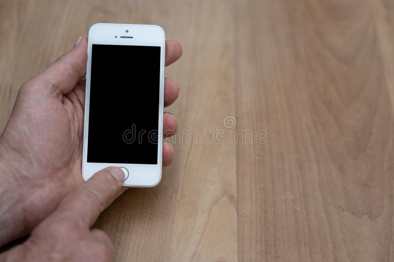 Human hand holding and operating a smart phone stock photo
