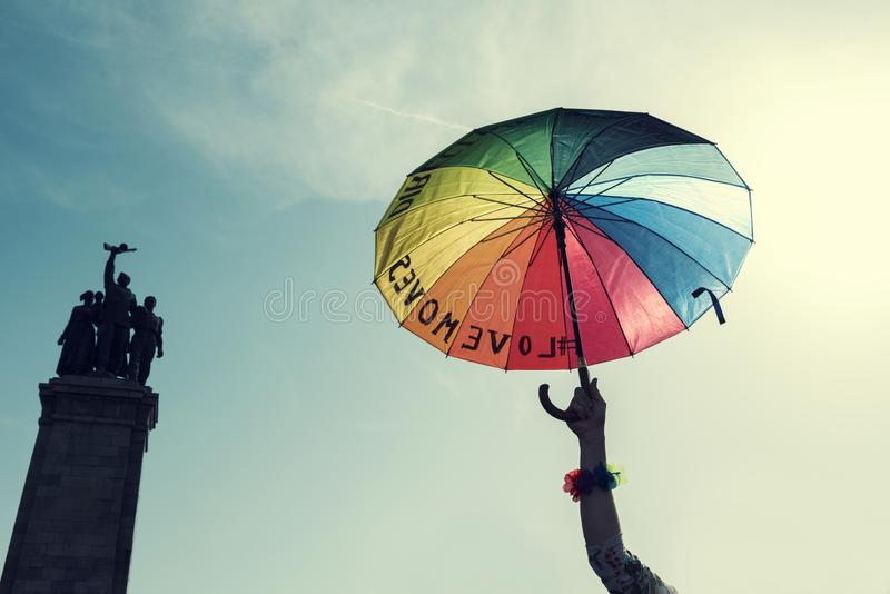 Human hand holding Pride rainbow umbrella in the sky next to Monument of Soviet army in Sofia royalty free stock images