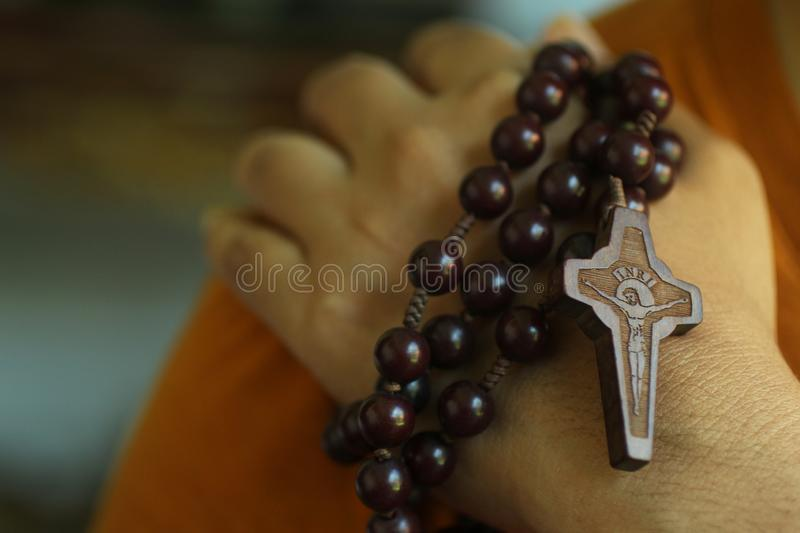 Human hand holding a rosary on the shoulder closeup. Junior young man hands praying holding a rosary with Jesus Christ Cross or stock image