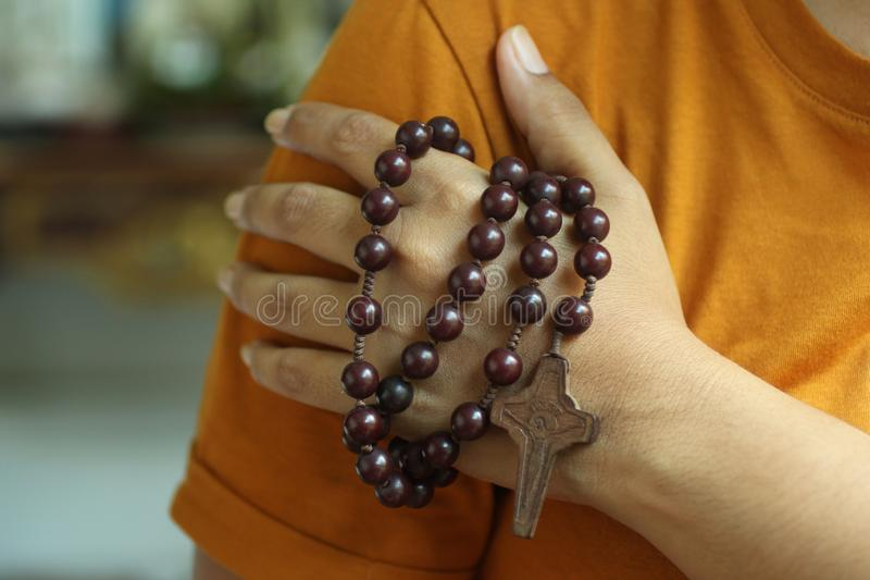Human hand holding a rosary on the shoulder. Junior young man hands praying holding a rosary with Jesus Christ Cross or Crucifix. stock photography