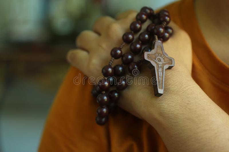 Human hand holding a rosary on the shoulder. Junior young man hands praying holding a rosary with Jesus Christ Cross or Crucifix. royalty free stock images