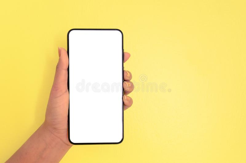 Human hand holding smartphone with white screen background stock images