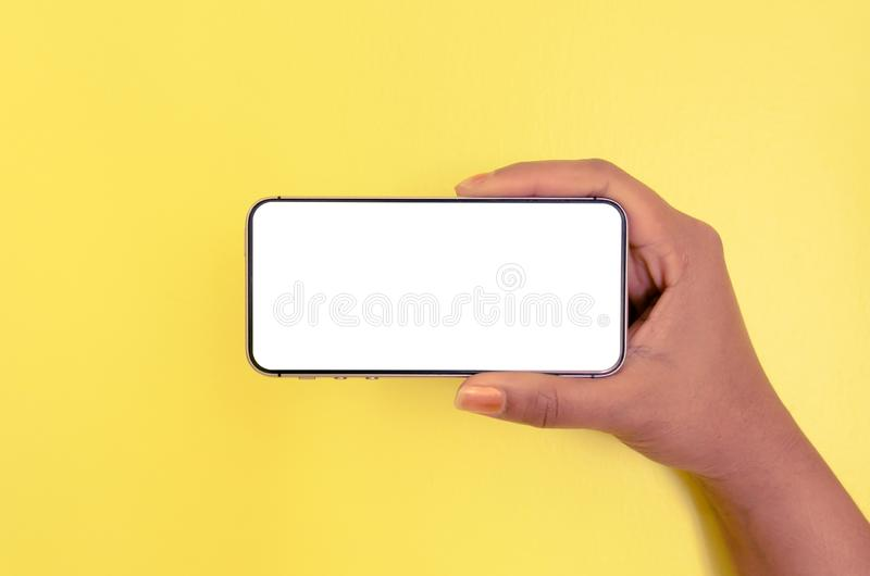 Human hand holding smartphone with white screen background royalty free stock image