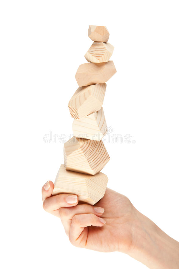 Human hand holding tower made of wooden blocks. (Japanese game tumi-ishi); illustrating concept of business success, achievements and self-control; isolated royalty free stock image