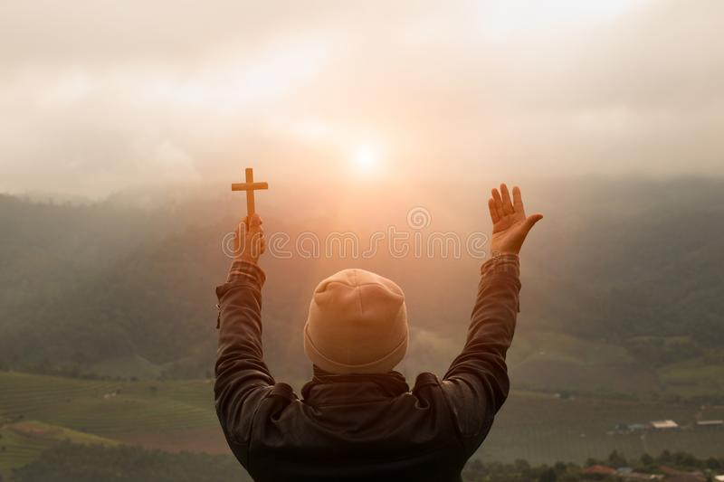 Human hand holds cross and open palm up worship. Eucharist Therapy Bless God Helping Repent Catholic Easter Lent Mind Pray. Chris. Tian concept background stock photo