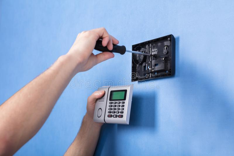 Human Hand Installing Security System. On Blue Wall royalty free stock images