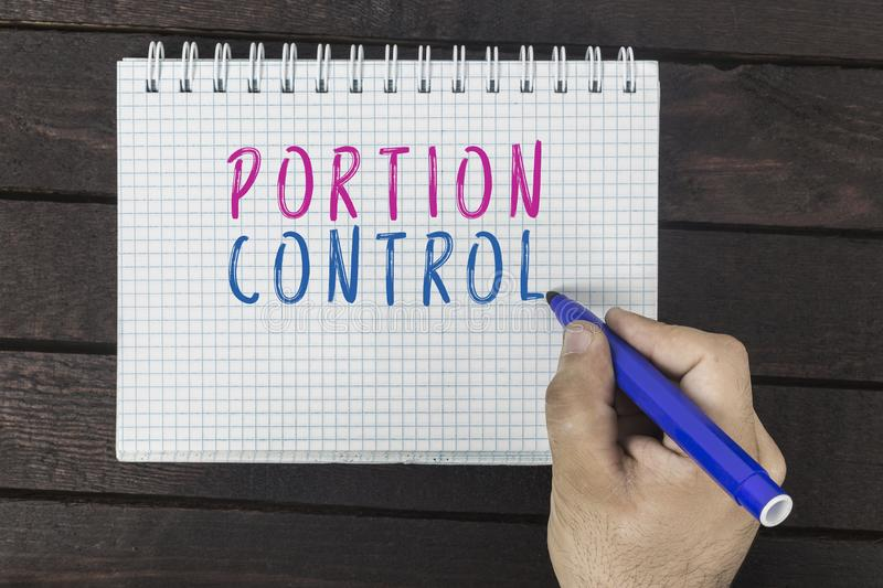 Human hand with marker writing text on notepad: Portion Control royalty free stock image