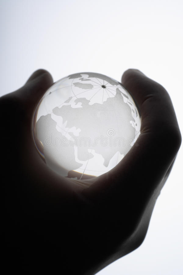Human hand with medical gloves gripping glass globe. Against white background,close up stock image