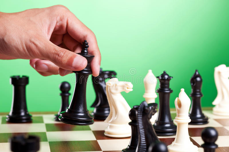 Human hand moves king on chessboard. Green background stock photos