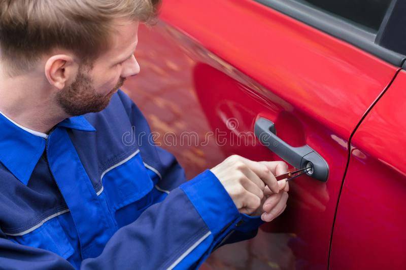 Human Hand Opening Car`s Door With Lockpicker stock image