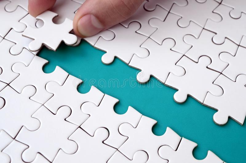 The human hand paves the way to the surface of the jigsaw puzzle, forming a blue space. The concept of overcoming the difficulties. On the way to success stock photography