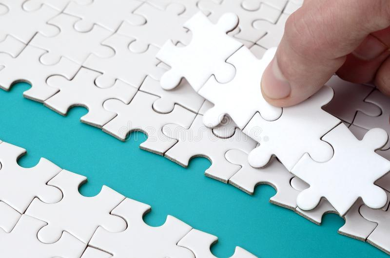 The human hand paves the way to the surface of the jigsaw puzzle, forming a blue space. The concept of overcoming the difficulties. On the way to success royalty free stock image