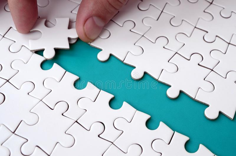 The human hand paves the way to the surface of the jigsaw puzzle, forming a blue space. The concept of overcoming the difficulties. On the way to success royalty free stock photos