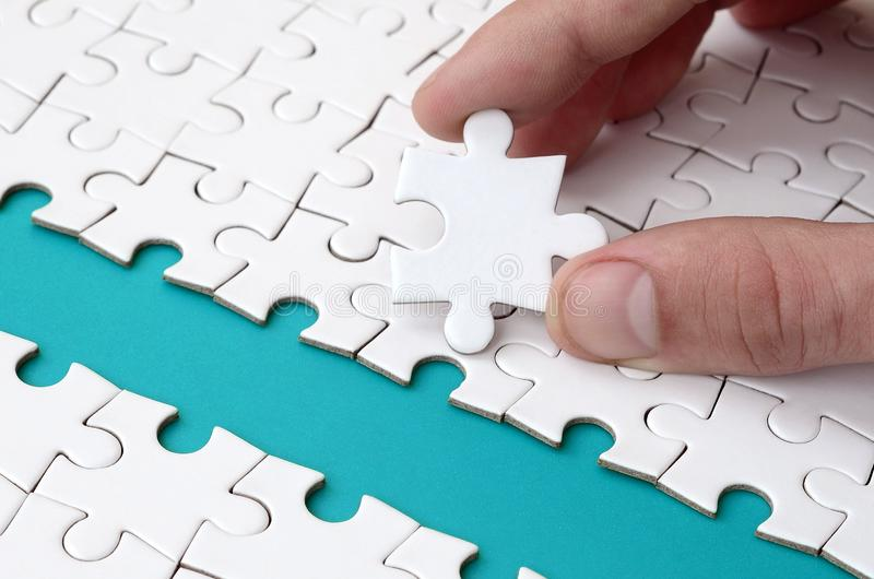 The human hand paves the way to the surface of the jigsaw puzzle, forming a blue space. The concept of overcoming the difficulties. On the way to success royalty free stock photography
