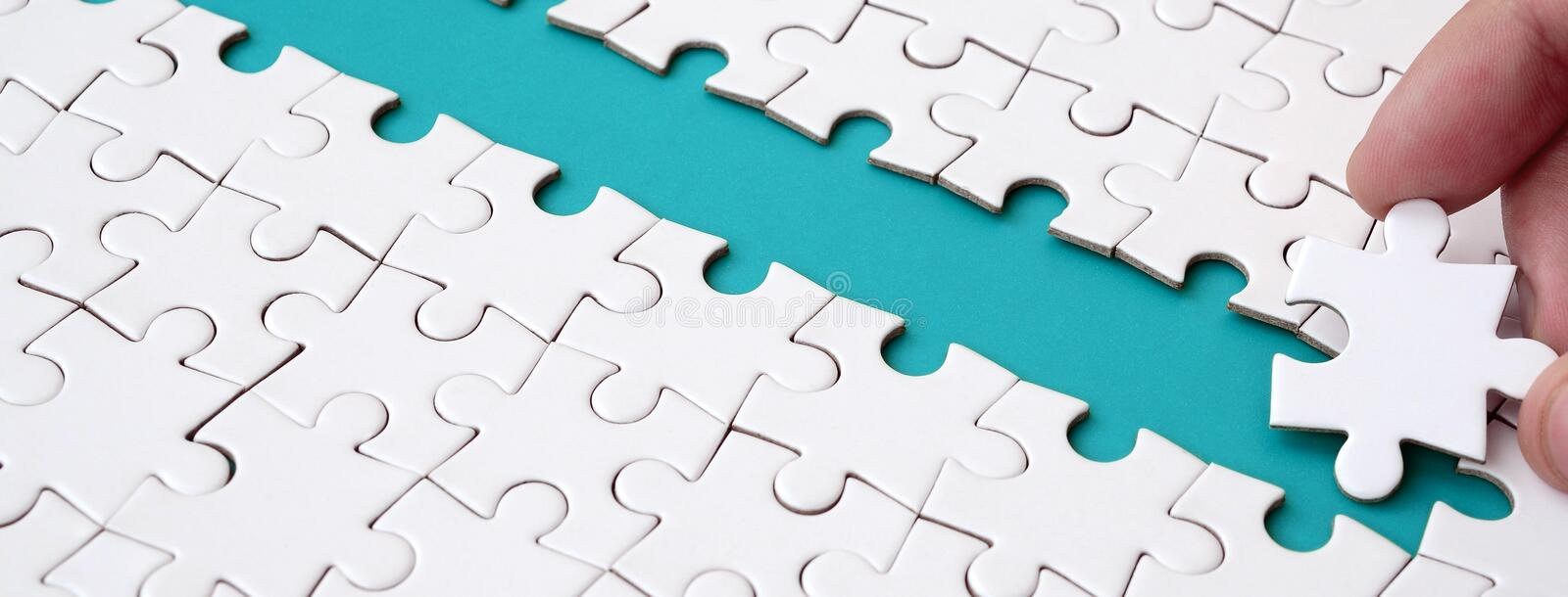 The human hand paves the way to the surface of the jigsaw puzzle, forming a blue space. The concept of overcoming the difficulties. On the way to success stock photo
