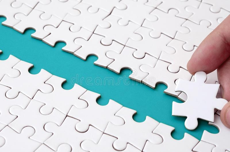 The human hand paves the way to the surface of the jigsaw puzzle, forming a blue space. The concept of overcoming the difficulties. On the way to success stock images