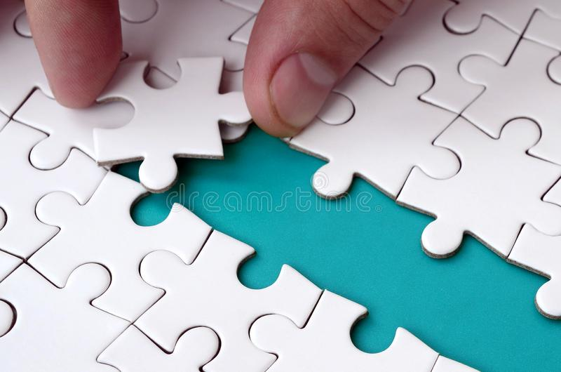 The human hand paves the way to the surface of the jigsaw puzzle, forming a blue space. The concept of overcoming the difficulties. On the way to success stock image