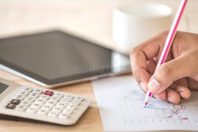 Human hand with pen calculating budget. Teacup and digital table stock photo