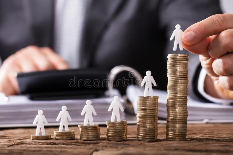 Human Hand Placing Human Figure On Increasing Stacked Coins stock photography