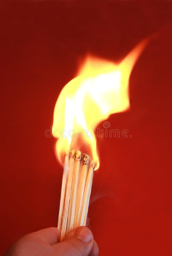 Human hand playing with fire. Playing with fire, hand holding large matchsticks just inflamed, high flame stock photography