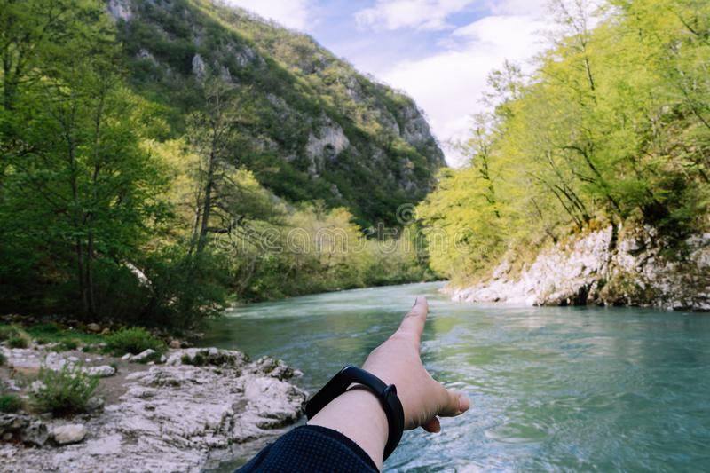 Human hand pointing with a finger in nature next to a river. Valley Tara River, Durmitor National Park, Montenegro. Clean water. Canyon. Smart watch girl hand stock photos