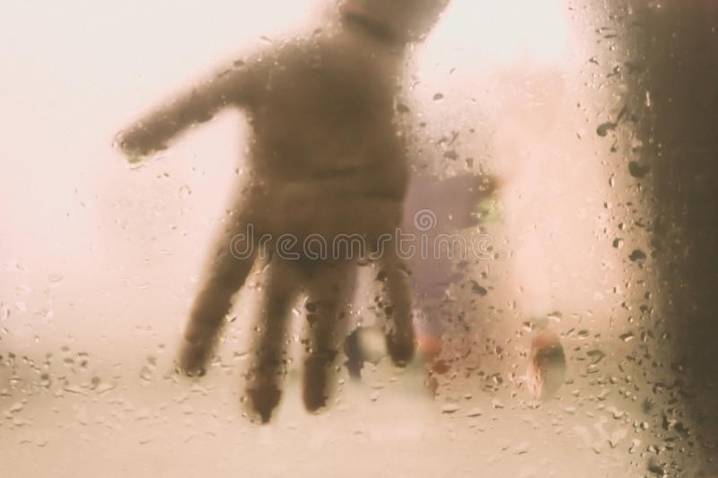 Human Hand pressed against a window with Drops Of Rain on it. Hand touching clear glass with water droplet. Natural Pattern of. Raindrops  from outdoor cloudy royalty free stock image