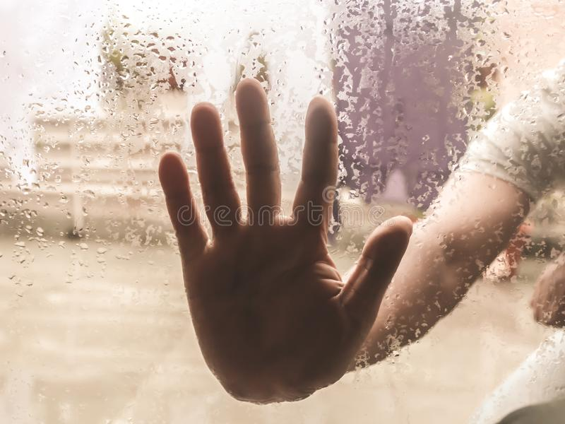 Human Hand pressed against a window with Drops Of Rain on it. Hand touching clear glass with water droplet. Natural Pattern of. Raindrops  from outdoor cloudy stock image