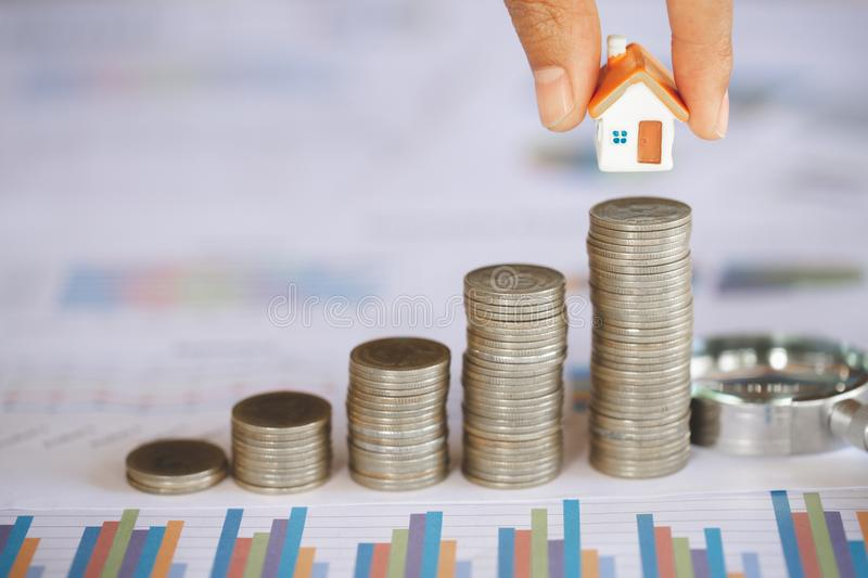 Human hand putting house model on coins stack. Concept for property ladder, home and residence, mortgage and real estate. Investment stock photography