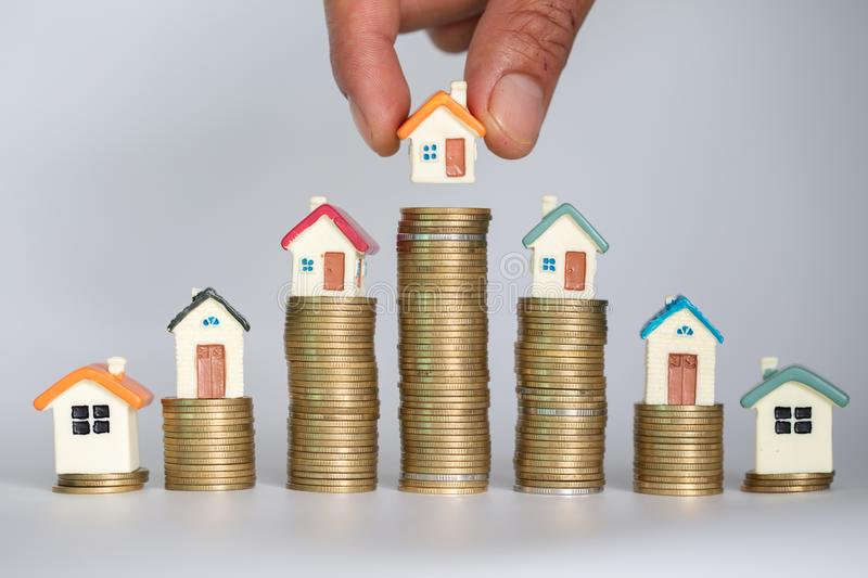 Human hand putting house model on coins stack. Concept for property ladder, mortgage and real estate investment.  stock images