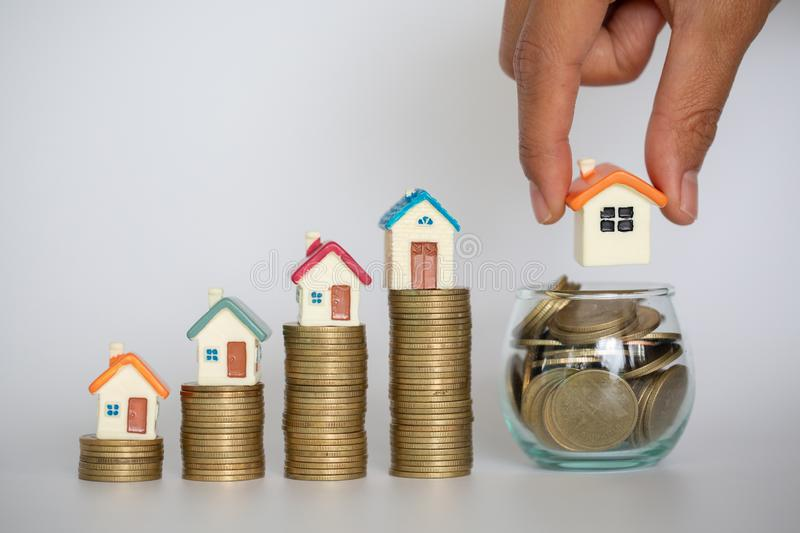 Human hand putting house model on coins stack. Concept for property ladder, mortgage and real estate investment.  royalty free stock photos