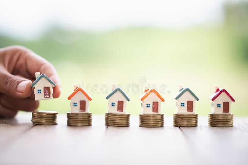 Human hand putting house model on coins stack. Concept for property ladder, mortgage and real estate investment stock images