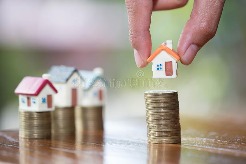 Human hand putting house model on coins stack, planning savings money of coins to buy a home concept, mortgage and real estate. Investment. saving or investment royalty free stock image