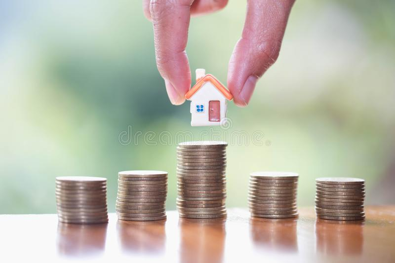 Human hand putting house model on coins stack, planning savings money of coins to buy a home concept, mortgage and real estate. Investment. saving or investment royalty free stock images
