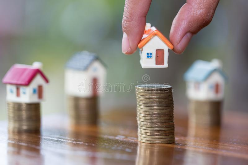 Human hand putting house model on coins stack, planning savings money of coins to buy a home concept, mortgage and real estate. Investment. saving or investment royalty free stock photography