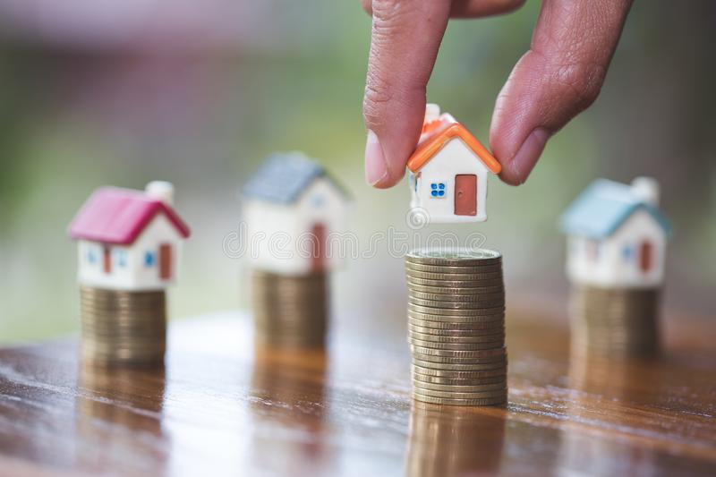 Human hand putting house model on coins stack, planning savings money of coins to buy a home concept, mortgage and real estate. Investment. saving or investment stock image