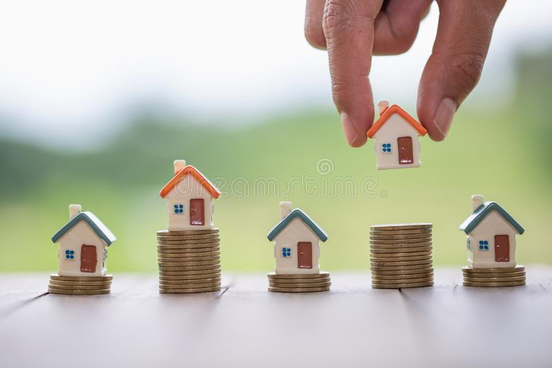 Human hand putting house model on coins stack,  planning savings money of coins to buy a home concept, mortgage and real estate stock image