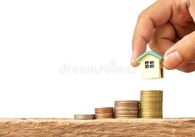 Human hand putting house model on coins stack royalty free stock image