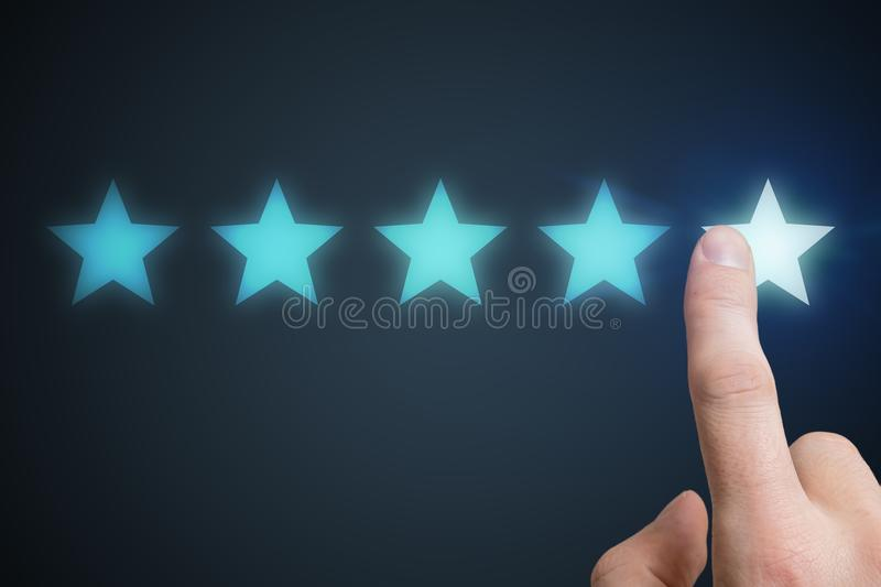 Human hand is rating with 5 stars. Ranking and customer satisfaction concept stock photo