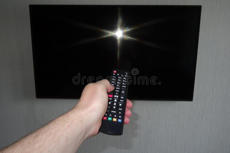 Human hand with a remote control in front of a black tv ice. On a gray background stock photo