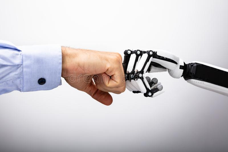 Human Hand And Robot Making Fist Bump. On Gray Background royalty free stock photography